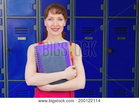 Digital composite of female student holding folders in front of lockers