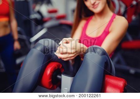 Close-up of the girl's hand, which pumps the press in the gym. The concept of doing sports, copyspace