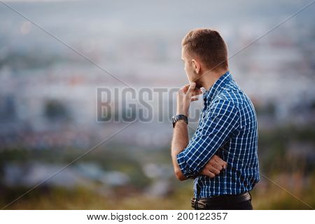 Portrait of a stylish man with a clock in a plaid hipster shirt on a blurred background. copyspace