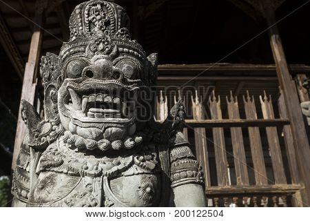 stone spirit statue detail in front of wooden fence at temple Pura Samuan Tiga, Ubud, Bali, Indonesia