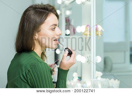 Beautiful brunette woman paints the lips. Beautiful woman face. Makeup detail. Woman's face with fashion pink lips makeup. Make-up artist apply pink lipstick