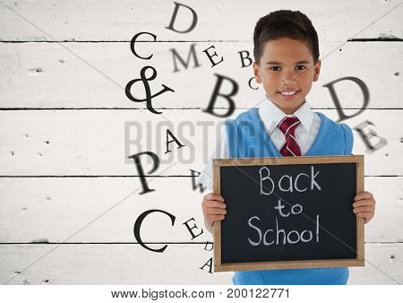 Digital composite of Many letters around Schoolboy holding blackboard with Back to school text