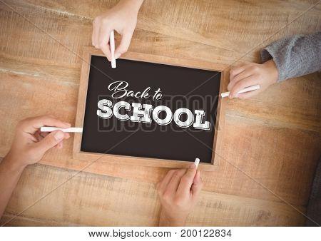 Digital composite of Hands writing Back to school on blackboard