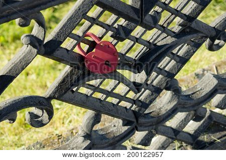 A red lock in the form of a heart attached to a fence. The symbol of the eternal love of the marriage