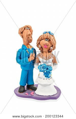 Clay figurine of a bearded bridegroom in blue and a bride in white isolated on white background