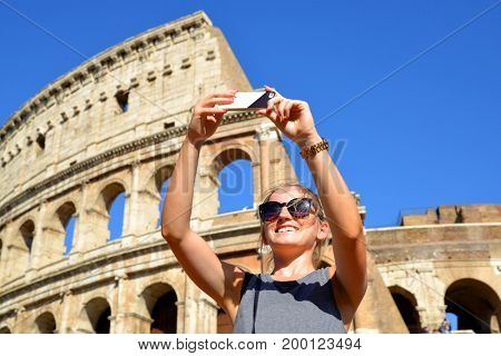 Happy girl making selfie in front of colosseum in rome, italy