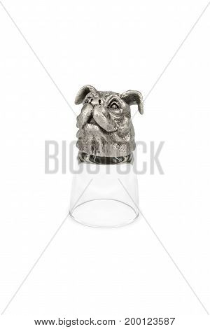 Decorative glass for vodka with a muzzle of a dog, turned upside down, isolated on a white background