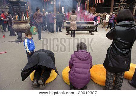 People praying to Buddha in temple