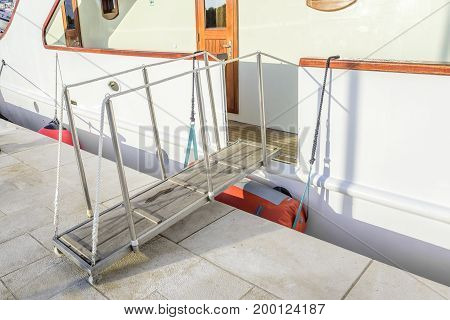 The gangway descended to the wharf from the white ship.