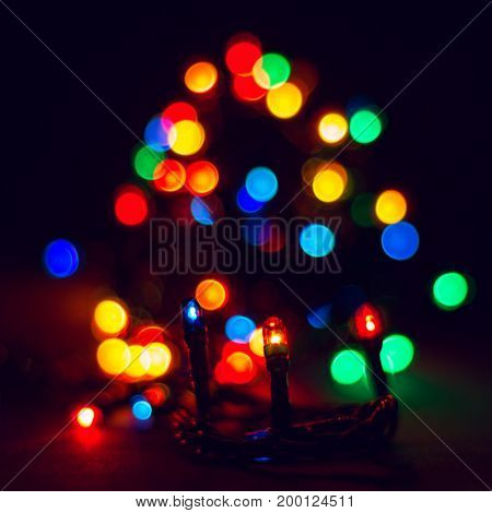 Bright lights of Christmas garlands in sharpness and in blur holiday atmosphere