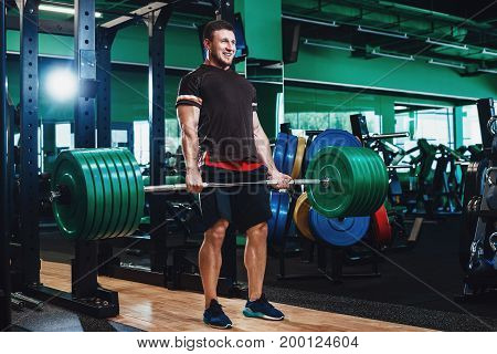 Young powerful muscular bodybuilder training with weight at sporting gym. Muscular Man Lifting Some Heavy Barbells