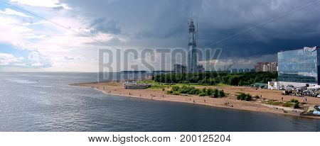A skyscraper under construction on the seashore under the sky changing from blue to a thunderstorm in St.Peterburg.panorama