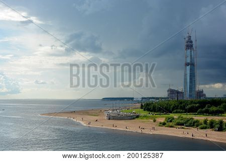 A skyscraper under construction on the seashore under the sky changing from blue to a thunderstorm in St-Peterburg.