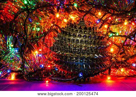 bright Christmas background with a shiny toy and glowing multicolored garlands the beauty of a holiday evening
