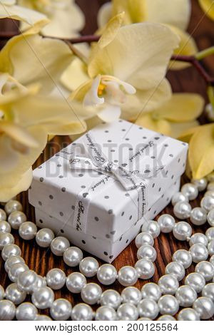 Gift box on a background of yellow orchids and pearls