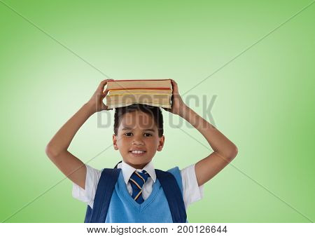 Digital composite of Schoolboy holding books in front of green background
