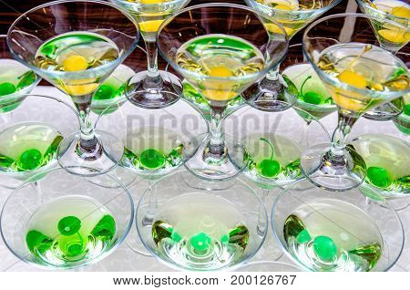 Alcoholic cocktail with green and yellow cherries