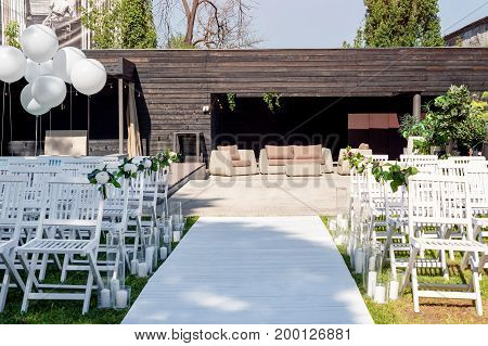 Beautiful wedding set up. Wedding ceremony in the garden. White wooden chairs decorated with flowers, balloons and candles standing in rows