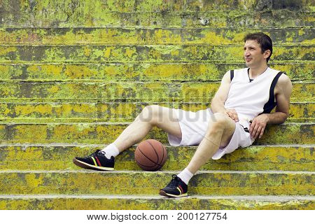 The basketball player is resting and sitting on the yellow green stairs with ball.
