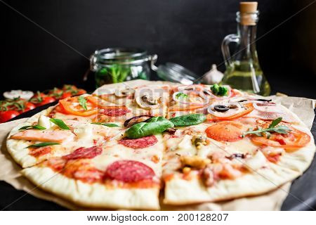 Pizza with ingredients, spices and cutlery on black background. Tasty pizza.