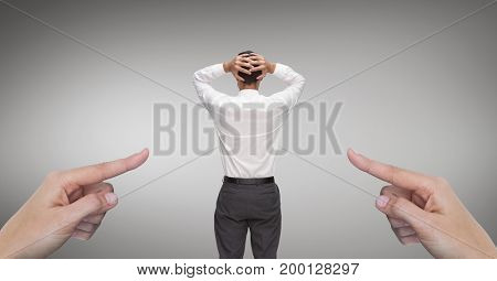 Digital composite of Hands pointing at surprised business man against grey background