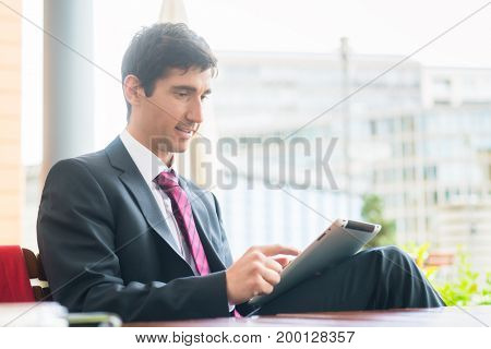 Young man wearing business suit while using a tablet PC during break in a cafeteria downtown