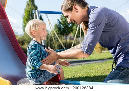 Woman and little boy chuting down slide at playground having fun
