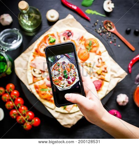 Tasty pizza with ingredients, spices and mobile phone isolated on black background. Flat lay, top view.