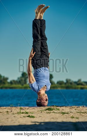 young yoga man doing a headstand on the riverside without holding hands