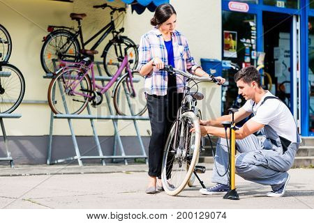 Bicycle mechanic inflating bike tire of customer in his workshop