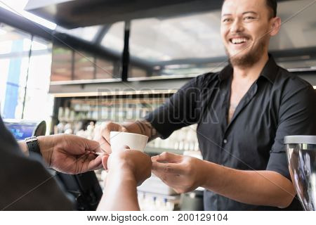 Friendly bartender serving espresso coffee to a middle-aged customer in the interior of a modern coffee shop