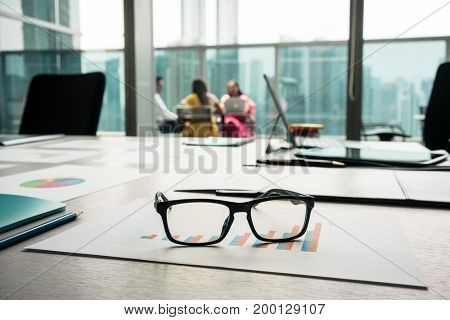 Close-up of eyeglasses on a printed bar chart showing progress in the interior of a modern business office