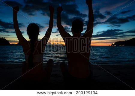Rear view of a young couple sitting on the beach with raised arms while feeling happy and free during summer vacation in Flores Island, Indonesia