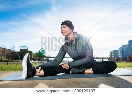 Young beautiful woman smiling while sitting down on a mat in a stretching position for the leg outdoors in a sunny day of summer