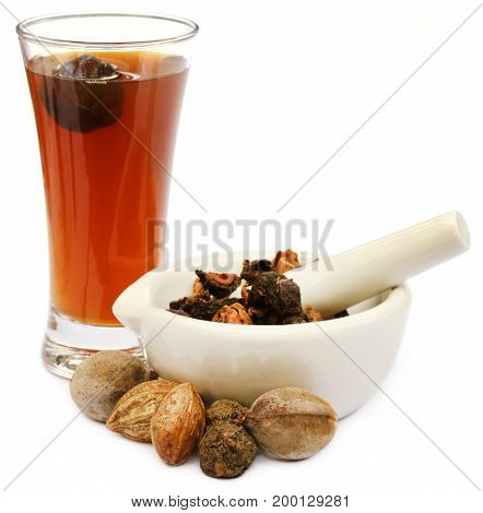 Ayurvedic extract of triphala fruits with mortar and pestle