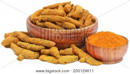 Whole and ground turmeric in wooden bowls over white background