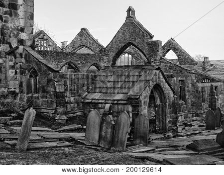 the ruined medieval church in heptonstall near hebden bridge in west yorkshire with stone walls gravestones and arches with pointed windows