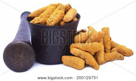 Whole turmeric with mortar and pestle over white background