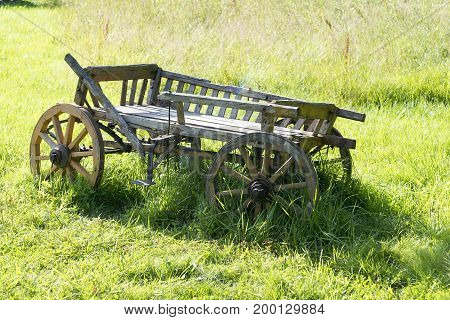 Old Wooden Wagon Stands On The Grass.