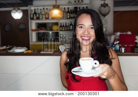 Laughing caucasian waitress with coffee working in a bar