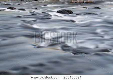 Smooth flowing water in stream with rocks