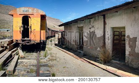 The abandoned railway wagons with damaged warehouse buildings