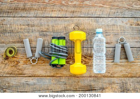 Fitness for losing weight. Dumbbells, expander, measure tape and water on wooden background top view.