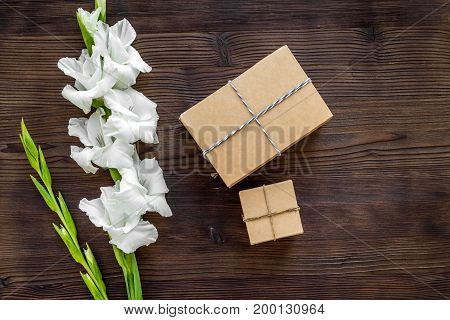 Gift box wrapped in craft paper near flower gladiolus on wooden background top view.