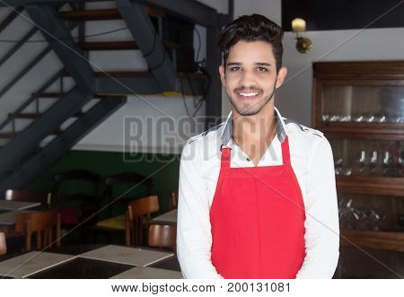 Handsome hispanic waiter looking at camera at restaurant