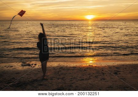 Silhouette of a woman at sunset by the sea with a kite in hands. Girl launches a kite on the beach in the evening. copy space for your text