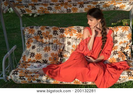 A Young Girl In A Red Dress Is Resting On A Country Swing