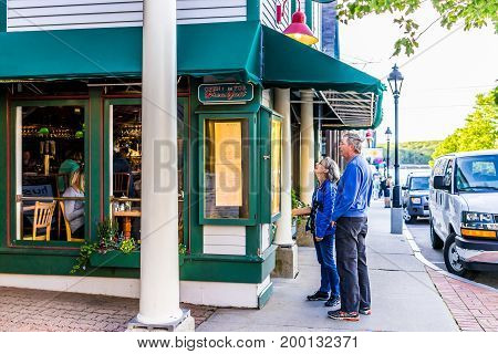 Bar Harbor USA - June 8 2017: Couple standing on sidewalk in downtown village in summer looking at restaurant menu