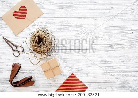 Packaging gift. Gift boxes, sciccors, thin cord, ribbon on grey wooden background top view copyspace.