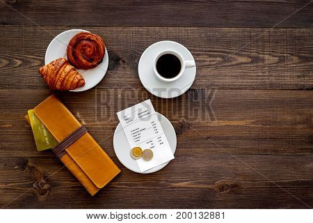 Pay bill at cafe by card. Purse, bill and bank card near coffee and croissant on dark wooden table top view.